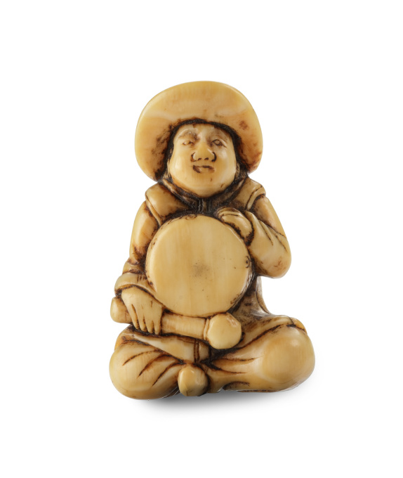 A SMALL IVORY NETSUKE OF A DUTCHMAN WITH A DRUM by Unknown Artist