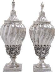 A pair of casted and embossed silver covered chest-nut vases